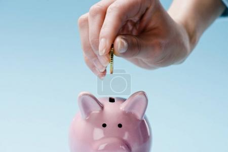 partial view of woman putting coin into pink piggy bank isolated on blue