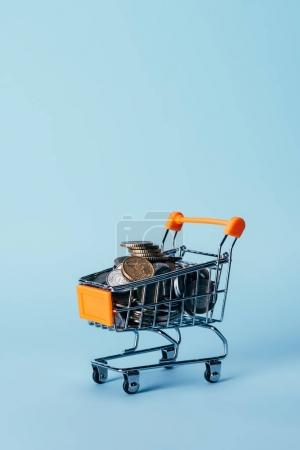 close up view of little shopping trolley full of coins isolated on blue