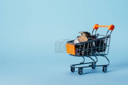Photo for Close up view of little shopping trolley full of coins isolated on blue - Royalty Free Image