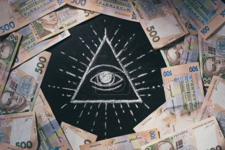 flat lay with arranged 500 hryvnia banknotes around Eye of Providence drawn on blackboard