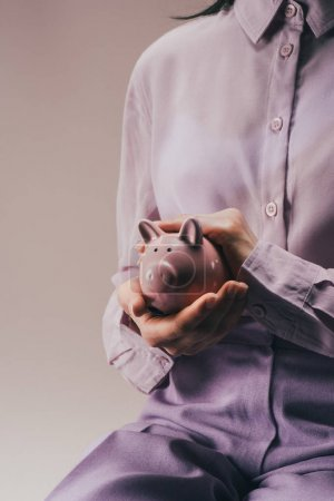 Photo for Partial view of woman holding pink piggy bank in hands isolated on lilac - Royalty Free Image