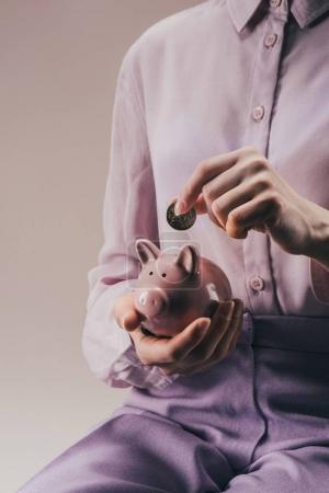 cropped shot of woman putting 50 euro cent into pink piggy bank in hand isolated on lilac