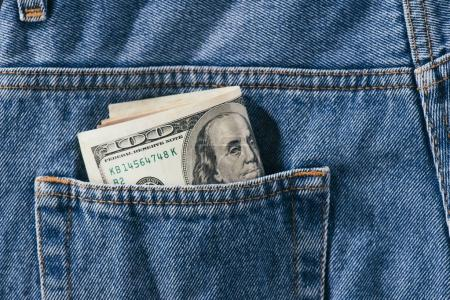 close up view of dollars banknotes in jeans pocket