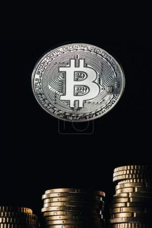 Close up view of silver bitcoin and stacks on cents isolated on black