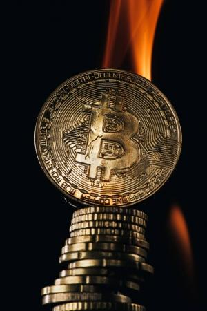 Close up view of golden bitcoins and fire isolated on black