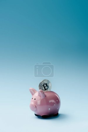 Close up view of pink piggy bank and silver bitcoin on blue backdrop