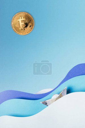 Close up view of golden bitcoin and paper ship sailing on blue paper waves isolated on blue