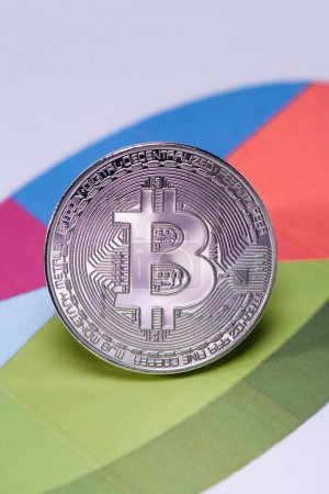 Close up view of silver bitcoin on colorful diagram