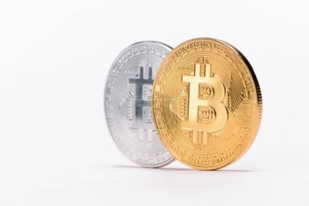 Close up view of silver and golden bitcoins isolated on white