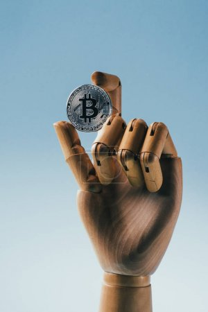 Close up view of wooden puppet hand holding silver bitcoin isolated on blue