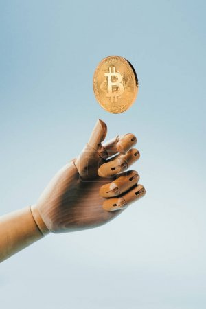 Close up view of wooden puppet hand and golden bitcoin isolated on blue