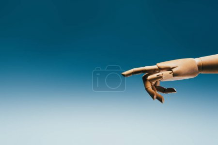 close up view of wooden puppet hand on blue backdrop