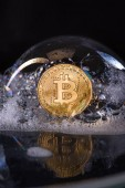 Close up view of golden bitcoin in soap bubble isolated on black