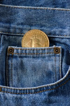 Close up view of golden bitcoin in denim pocket