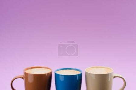 close up view of arranged colorful cups of coffee isolated on purple