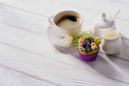 close up view of cup of coffee, tulip flower, sweet muffin and jag of cream on white wooden tabletop