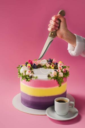 cropped shot of woman with knife, cup of coffee and decorated cake isolated on pink