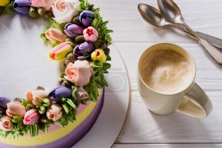 close up view of cup of coffee and floral decorated cake on white wooden surface
