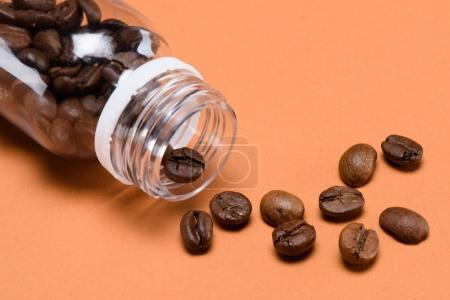 close up view of roasted coffee beans and plastic bottle isolated on peach