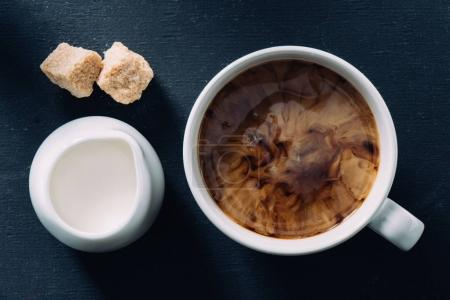 Photo for Flat lay with cup of coffee, jag of cream and cane sugar pieces on dark surface - Royalty Free Image