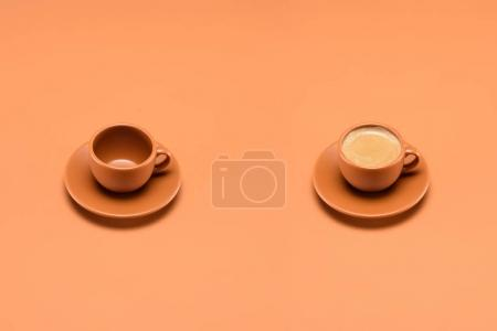 Photo for Close up view of empty cup and cup of coffee isolated on peach - Royalty Free Image