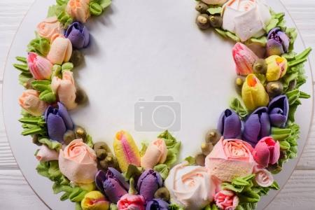 top view of cake decorated with cream flowers on white wooden surface