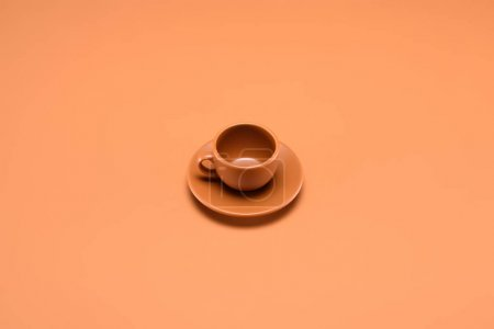 close up view of empty cup on saucer isolated on peach