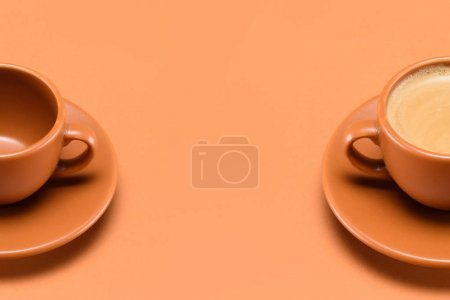 close up view of empty cup and cup of coffee isolated on peach