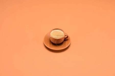 close up view of cup of coffee on saucer isolated on peach