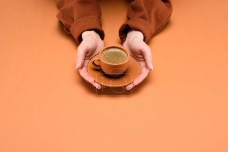 Photo for Cropped shot of woman holding cup of coffee on saucer in hands isolated on peach - Royalty Free Image