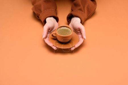 cropped shot of woman holding cup of coffee on saucer in hands isolated on peach