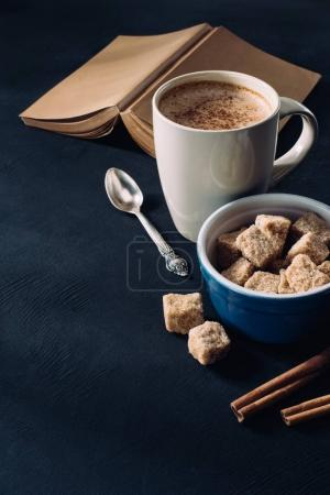 Photo for Close up view of book, cup of coffee, bowl with brown sugar and cinnamon sticks on dark surface - Royalty Free Image