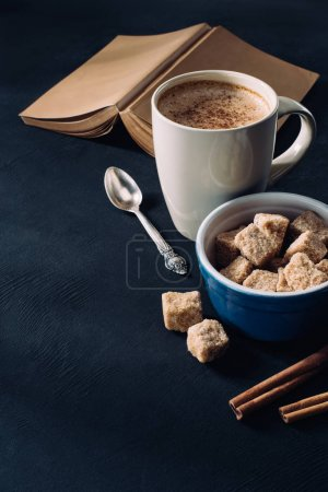 close up view of book, cup of coffee, bowl with brown sugar and cinnamon sticks on dark surface