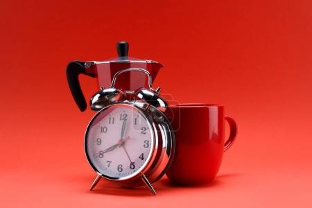 close up view of coffee maker, alarm clock and cup of coffee isolated on red