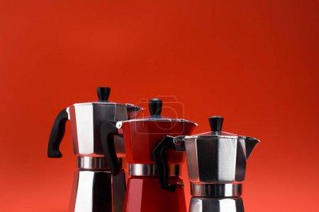 Photo pour Gros plan vue d'arrangement des cafetières isolé sur rouge - image libre de droit