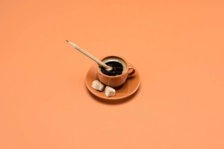 close up view of cup of coffee with pencil and cane sugar on saucer isolated on peach