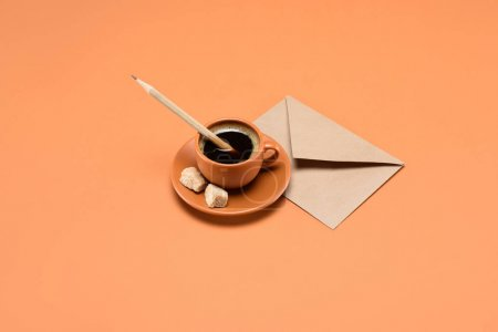 close up view of cup of coffee with pencil, cane sugar on saucer and envelope near by isolated on peach
