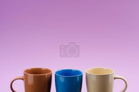 close up view of arrangement of empty cups isolated on purple
