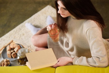 Photo for High angle view of woman with cup of tea and book at home - Royalty Free Image