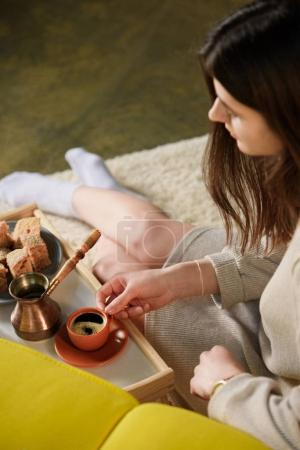 selective focus of young woman with cup of coffee on wooden tray at home