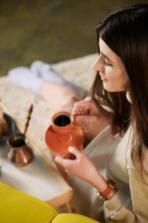 selective focus of young woman with cup of coffee at home