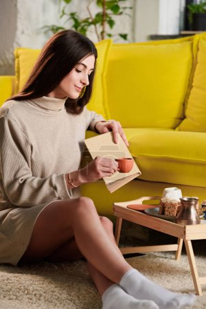 woman with cup of coffee and book at home