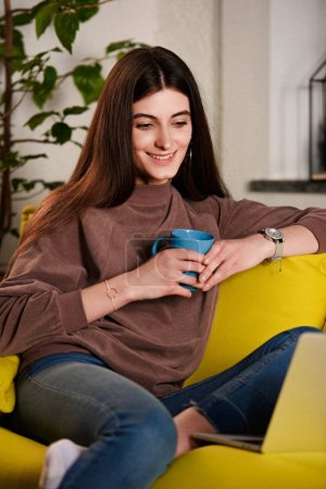 woman with cup of coffee using laptop on sofa at home