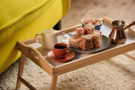 close up view of cup of coffee, jag of cream, pieces of cake and brown sugar on wooden tray in room