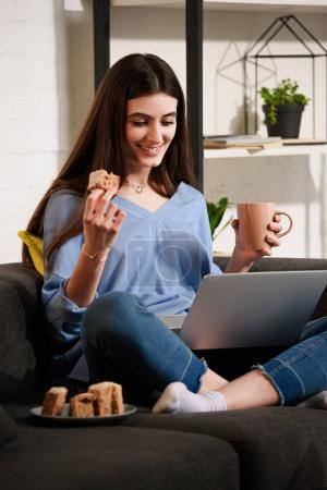 Photo for Smiling woman with cup of coffee and piece of cake using laptop on sofa at home - Royalty Free Image