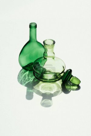 close up view of empty glass bottles and cork on white backdrop