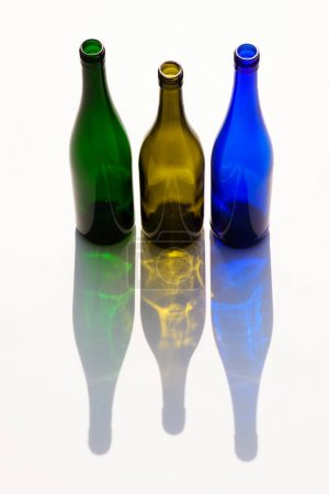 close up view of empty colorful glass bottles with shadows on white background