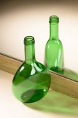 close up view of green glass bottle reflection in mirror