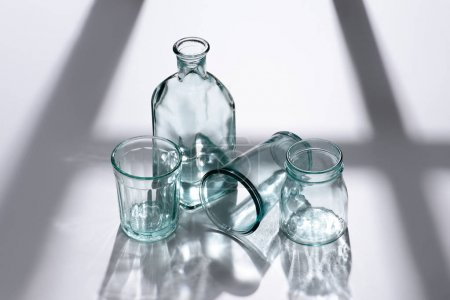 close up view bottle with water and empty glasses on white tabletop