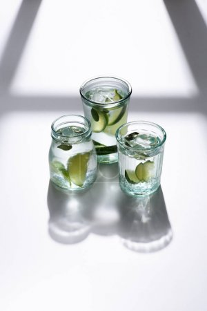 close up view of glasses with water, lime pieces and ice cubes on white tabletop